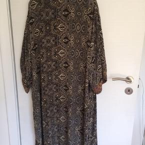 Ny og ubrugt kimono fra Sissel Edelbo.  Kimonoen er vendbar og har forskelige mønstre på for og bagside. Der står ikke materiale i men stoffet er glat og behageligt og jeg tror blot at den skal hænges våd op efter vask og så er den klar igen. Der medfølger et bælte.  Nypris kr. 1.100,00   MP 550,00 pp - Bytter ikke.