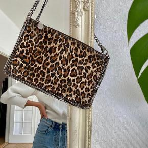 Fin clutch i vegansk leopard stof.  Lynlåslukning, logo twill foring, lynlås aftrækker med det ikoniske logo medalje. Ruthenium metal.  Højde: 15cm  Længe: 25cm Nypris 2.949 kr - BYD