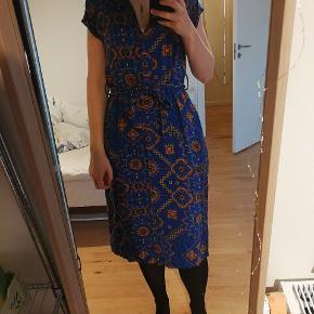 Den fineste moves kjole i så fint et print. Kjolen er størrelsessvarende, har bindebånd i taljen og slidser i begge sider. Der er knapper hele vejen og kan bruges åben som kimono.