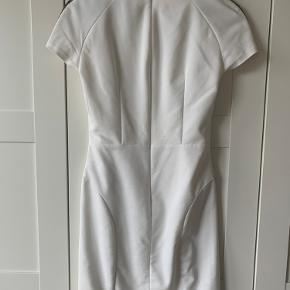 Smukkeste hvide kjole med perler på skuldrene - virkelig flot detalje. Kjolen er kropsnær og lynes på ryggen.