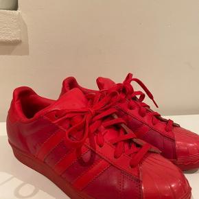 Røde sneakers fra Adidas, dog ret slidte