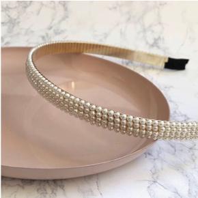 Perle hårbøjle med 3 rækker perler.  Har to stk. Prisen er 50 kr. pr. stk.   Fragt er 10 kr. med post nord, ønskes dao er prisen 31 kr.