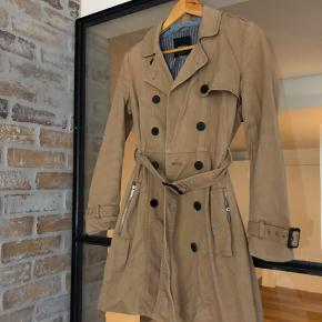 Beige trenchcoat. Worn but well-kept. Comes with a belt. Has little stains on the back side, nearly invisible (see last image).