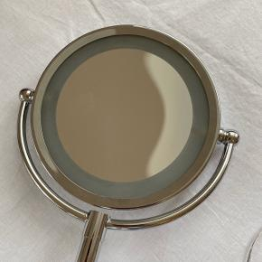 Flipspejl med lys i kanten  Har et almindeligt spejl og et forstørrende spejl  Spejlene måler ca. 15 cm I diameter  Foden måler 13 cm  Højde: ca. 35 cm   Fremstår som nyt og selve lyset i spejlet har været brugt meget få gange