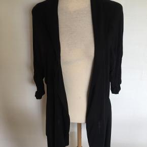 Smart cardigan uden knapper og med asymmetri forneden. Se foto.  Aldrig brugt eller vasket.  Bytter ikke. Se også mine øvrige annoncer. (18)