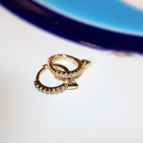 Zahara øreringe med én spike. De er lavet i 14 karat guldbelagt sterling sølv og ryddet med talrige små zirkoner. Måler ca. 8mm.  Detaljer Materiale  925 Sterling sølv belagt med 14 karat guld. Zirkon sten: Zirkon skal ikke forveksles med kubisk zirkonia. Zirkon er en naturlig sten, som er et godt alternativ til en diamant. Håndlavet i New York