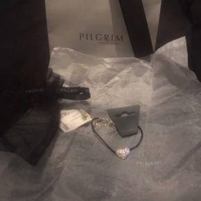 """#30dayssellout  Det smukkeste, tynde læder armbånd med glimtende sølv hjerte vedhæng fra Pilgrim. Jeg fik det i gave tilbage i 2013 men fik det aldrig byttet, da det ikke lige var mig alligevel, derfor sælges det videre da det er syndt det bare ligger i gemmeren.   Som man kan se er det købt i Magasin, standen er """"ny, med prismærke"""" da ALT medfølger, som vist på billederne; indpakning, gavepose, bytte-mærket, derfor altså ALDRIG blevet taget i brug 😊✨  Prisen kan jeg ikke se på byttemærket men tror det har ligget omkring de 300-350 kr.  Hvis det skal sendes, betaler køber fragt.  Mvh Betina Thy"""