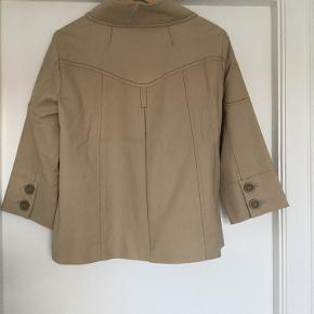 Fin beige kort jakke med 3/4 lange ærmer, længde til midt på hoften. Bomuld med 3% elastan.  Prisen er fast og bytter ikke.