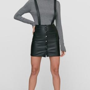 Super lækker og fræk læder nederdel med tilhørende seler og bælte. Selerne kan knappes af. Den er høj taljet og sidder bare så flot. Jeg kan desværre ikke passe den mere. Den passer str. 36-38.  Billedet af modellen er ikke den rigtige nederdel. Jeg vil blot vise looket. Jeg synes personligt denne nederdel jeg sælger er federe fordi stropperne er brede - kvaliteten er tyk og så har den et råt look med alle knapperne og spænderne.