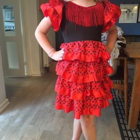 Flamenco-kjole i rød med sorte prikker, flæser og frynser. Passer str 7-8år ca. Til udklædning eller fastelavn.