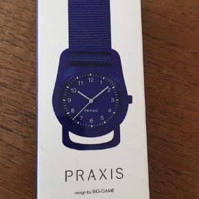 """Lækkert """"strap watch fra Praxis.  Det er unisex og passer til alle, da remmen kan indstilles.  Aldrig brugt og købt på MOMA i New York  Kan afhentes på Østerbro ellers sendes med DAO, hvor køber betaler porto  Praxis Ur Farve: Blå Oprindelig købspris: 230 kr."""