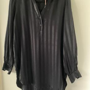 Smuk skjorte i sort med struktur striber.   Brystmål: 110 cm Længde fortil: 76 cm Længde bagtil: 85 cm  Desværre et fejlkøb og har ikke nået at bytte den i tide (har kvittering).