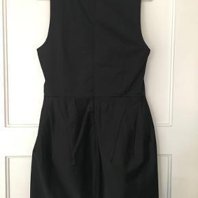 Tætsiddende kjole uden ærmer. Lynlås i ryggen. Rigtig lækker kvalitet og fine detaljer med små syninger.
