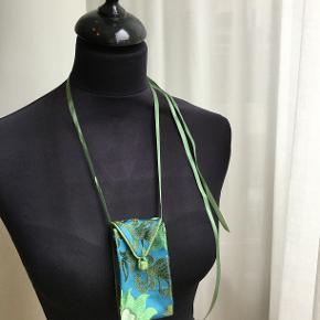 Håndsyet vintage halstaske i 100% brokade silke. Tasken har justérbart bånd som ligeledes er i silke. Længde 12, bredde 6 og dybde 2 cm.