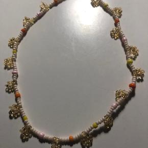 Perlehalskæde i beige seadbeads m store perler i orange lyserød og gul og guld blomster 💮 prisen er 65kr inkl Porto