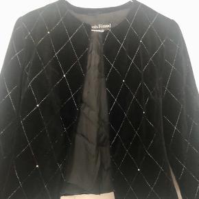 Smukkeste vintage lille jakke fra den franske designer Louis Féraud. Jakken er i dybsort blød velour med mønster af små sølvnitter og sølvtråd. Fransk 36, passes af en 34 og lille 36. 440 inkl.