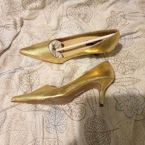 Pumps i guld-look, som aldrig er brugt. Kan ses på sålerne. De er som nye.