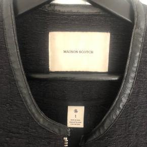 Jakke fra Maison Scotch med sølv lynlås. Selve stoffet har tekstur. Brugt i en periode og har derfor tegn på vask og mindre slid på læderet i nakken. Lommerne er gået op indvendigt i syningen, hvilket dog kan sys. Derudover i god stand.