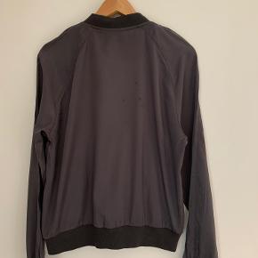 Blød jakke med lynlås i smuk grå. Et par små pletter bagpå (se billede).