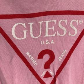 Guess tee i lyserød, den er brugt og man kan godt se den er falmet i farven + noget slid på logoet på brystet