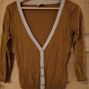 Mørk karrygul cardigan med lysegrå kant og skinnende knapper. Lommer. Blødt strik med silke i.
