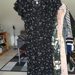 Kjole fra H&M i str. 34.  Elastik og bindebånd om taljen.  Cirka mål: Længde (fra hals til hæm): 87 cm Talje: 36 cm Armlængde: 12 cm Skulder til skulder: 33 cm