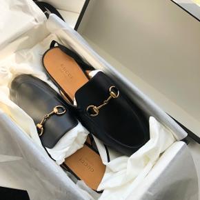 Sælger mine Princetown leather slippers Ny pris 4.300kr. Mindste pris 3.600kr  De er str. 37.5, men passer en 37 De er blevet forsålet, hvilket har kostet 350kr. Alt medfølger ( kvittering, kasse, dustbags osv. ) De er i virkelig god stand, købt den 20. Maj på Gucci.com