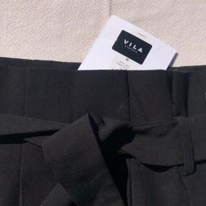 Flot elegant nederdel med indbygget bæltedetalje. Aldrig brugt.
