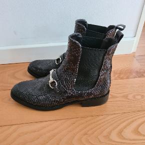 """Lækre chelsea støvler med sølvspænde i grå-sort """"slangeskind"""". Fin stand, ikke brugt meget. Rundt omkring har skællene løftet sig lidt og er røget af enkelte steder. Bud fra 500 kr + forsendelse."""