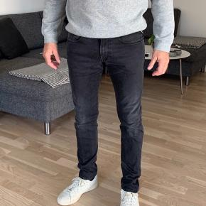 Fede jeans fra Replay i str. 31/32. Farven er grå/sort og med strech.  Nypris: kr. 1.200.