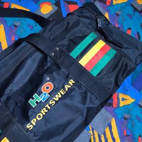 Lækker retro H2O taske af den helt gamle slags! Det kan dog ikke ses på den, da den er i god stand.  Tasken er cirka 60x25x25 og vil garenteret få alle dine venner til at misunde din fede vintage stil!   Se også mine andre annoncer med retro trøjer, jakker og tasker fra f.eks. H2O, Nike og adidas 😉