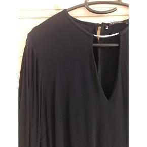 Fin bluse i sort med åben detalje ved brystet. Som ny