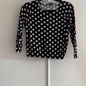Black polkadot sweater from Topshop. The front has beading detail on some of the polkadots. Some beads are loose but have been loose for some time and none have ever fallen off. It goes in the washing machine. The size within the sweater is 42 but the actual size is about size 36.