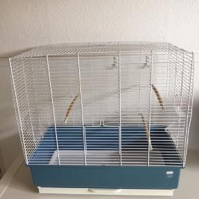 Stort flot fuglebur, brugt til undulater. Hvid med blå. måler ca 60x57x33 cm, vi har haft 3 undulater i den. I hver side er der vandskåle. Nypris 699kr