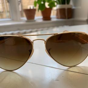 Ray-Ban Solbriller Aviator - Guld   Detaljer: - Pilotbriller i guld - brune, graduerede glas. - Stelbredde 130 mm. - Justerbare   Stand af solbriller - Milde, men få ridser i brilleglasset  - God stand men brugt  Yderligere information: - Købt i Københavns lufthavn - Original solbrille etui medfølger - 100% UV-beskyttelse