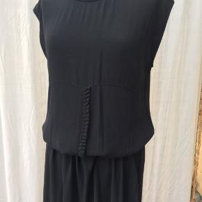 Dejlig kjole i enkelt snit. Materialet er 100 % viscose. Kjolen kan stiles op med smykker og længden evt reguleres med bælte.  Bryst: ca 2x52 cm Længde: ca 135 cm Hofte: ca 2x 63 cm  Kan sendes med DAO for 38kr.