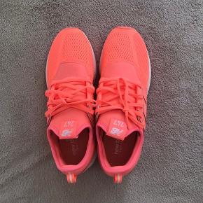 Neon coralfarvede sneakers, dame str.41 , model : NB247, lidt sort bag på den ene sko, ses kun på nærbillede, kan muligvis vaskes af. Aldrig brugt, kun prøvet. Bytter ikke.