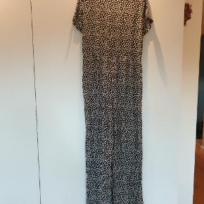 Skøn buksedragt med lynlås i siden, knapper og bindebånd foran. Skrålommer og vide ben