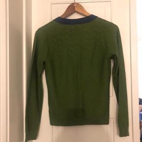 Fed tofarvet cardigan med store, blanke knapper. Har kun brugt den en enkelt gang eller to, og den fremstår som ny.   Materiale: 50 % acrylic, 50 % wool.