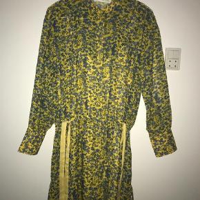 Varetype: Midi Farve: Gul Oprindelig købspris: 1500 kr.  Pieszak kjole /tunica . Har købt denne smukke kjole i det flotteste gul/blå blomstrede print i  fin tynd kvalitet med underkjole i 100% polyester kan vaskes på 30`fin med længde til lige over knæet er gennem knappet og har fint bånd i taljen som kan give facon , sælger vi mobilpay og sender med Dao inden for 24 timer .