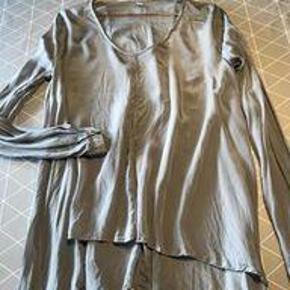 Varetype: Bluse Farve: Grå  Super fin bluse fra 2nd Day. Grå viscose og lange ærmer som lukkes med 2 små knapper. Længde for ca 60cm og bag ca 75cm. Sjov detalje på ryg med 2 syninger på ryggen.    MP kr. 150
