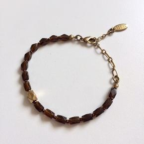 Fint armbånd med brune perler samt en enkelt guldfarvet.  Justérbar længde. Bly- og nikkelfri.