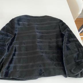 Super fin kort fake fur 100%polyester jakke. Fine detaljer på ærmerne.