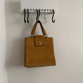 Vintage Chanel taske, købt på Rue de Turenne i Paris for ca. seks år siden. Den har været flittigt brugt og viser tydelige tegn på slid - men den er absolut ikke tømt for brug og har er tidløst og unikt design. Den ville have godt af lidt pleje, men kan også godt tåle patina - se billeder. Den duer til alle outfits og farver.