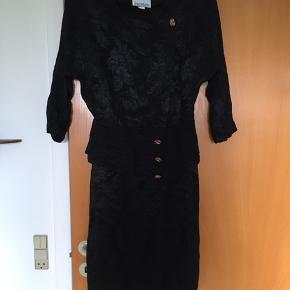 Super flot 80'er retro - vintage kjole med skulderpuder og let skinnende stod med blomsterprint. Kjolen er meget smuk og sidder godt. Mål: længde 102 cm, bryst: 2*47 cm, talje: 2*38 cm.