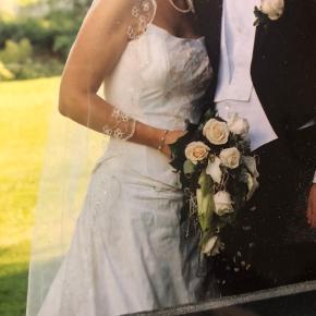 Brand: Karim Varetype: brudekjole Størrelse: M syet Farve: se foto  Den smukkeste kjole designet af Karim selv. Der er super mange flotte detaljer og det smukkeste slør. Byd
