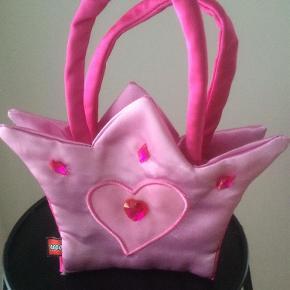 Varetype: Prinsessetaske Størrelse: 10/10 Farve: Lyserød/pink Prisen angivet er inklusiv forsendelse.  Flot taske i lyserød med pinkfoer og trykknap fra Lego.   Der er løbet en en tråd foroven i venstre side under den pinkesten. Se billed 4.   Lego har syet lidt skæv i den ene side. Se billed 3