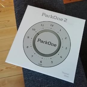 """ParkOne 2 parkeringsskiveHaves i sort og silver titanium.   Fuldstændig ny og ubrudt emballage.  Nypris ligger på 260,- billigste sted på nettet.  Sælges for 169,- pr. stk. (199,- inkl. porto).  Mere info: FUNKTIONEL OG SMUK ParkOne 2 er designet med enkle smukke linjer kombineret med intuitivt funktionelle detaljer. Fronten er letlæselig, og proportionerne er velafbalancerede, så stilen ligger i tråd med formsproget i moderne biler. Bagsiden er ligeledes enkel uden overflødige detaljer. Det runde tema går igen i den centralt placerede detalje, som også er en knap til fremrykning af tiden. Detaljen er desuden et låg, der let klikkes af for adgang til batteri og tidsindstilling.  VINKLET INDERDISPLAY På bagsiden af ParkOne 2 er displayet vinklet for at lette aflæsningen af tallene. På mange nyere biler sidder forruden skarpt vinklet, og instrumentbordet er dybt. Her kan det være svært at aflæse et display, som vender nedad. Også dette er løst med ParkOne 2.  ENKEL BETJENING ParkOne 2 betjenes enkelt med kun to knapper. Den ene er den store runde knap på bagsiden, som fungerer på to måder; i parkeringstilstand kan man stille tiden frem ved at trykke på knappen, og klikkes """"knappen"""" af, kan tid og dato indstilles via de to knapper, som kommer til syne. Batteriet skiftes også enkelt, når det er brugt op."""