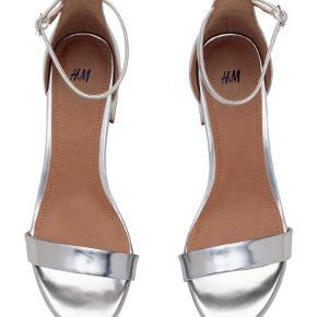 Sandaler, str. 41, H&M, Sølv, Imiteret læder, Ubrugt Super fine sølvsandaler i imiteret læder. Ankelstropperne er justerbare. De er helt nye og ubrugte med mærkesedler. Hælhøjde: 6 cm. De er normale i størrelsen. Købspris: 249,95 Det sidste billede er mine egne sølvsko Eventuel fragt lægges oveni.