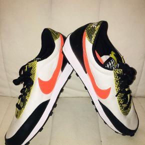 Hvide, orange, gule og sorte sneakers fra Nike. Størrelsen er en 41. Modellen er Daybreak. Ingen kasse desværre men helt som nye.
